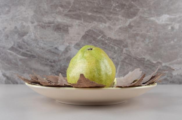 Birne auf platanenblättern in einer platte auf marmor