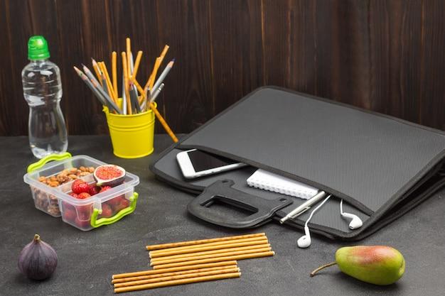 Birne, essbare strohhalme und feigen auf dem tisch. schwarze aktentasche mit smartphone und notebook.