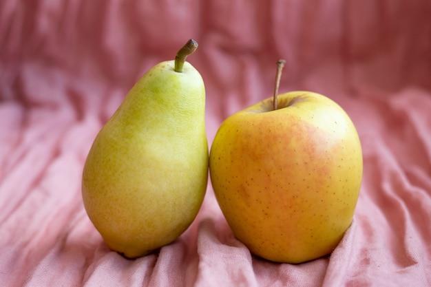Birne und apfel auf einer rosa stoffoberfläche