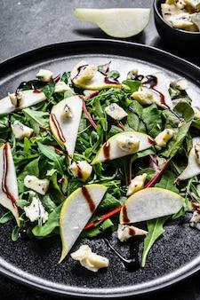 Birnen-, blauschimmelkäse-, rucola- und nusssalat auf teller. schwarzer hintergrund. draufsicht