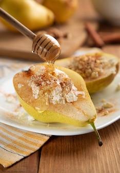 Birnen mit hüttenkäse, nüssen, honig und zimt auf weißem teller. es wird mit honig gewässert.