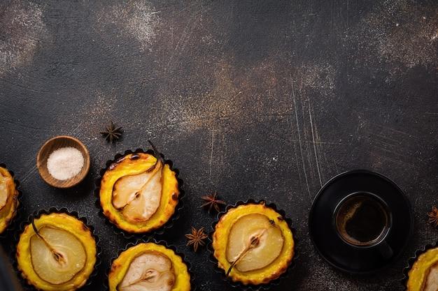 Birnen und vanillepudding-minitörtchen auf einem dunkelbraunen alten tischhintergrund aus beton. ansicht von oben.