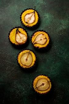 Birnen und vanillepudding-minitörtchen auf einem dunkelgrünen alten tischhintergrund des betons.
