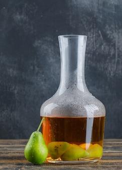 Birnenmosttrink mit birne in einer flasche auf hölzerner und schmuddeliger wand, seitenansicht.