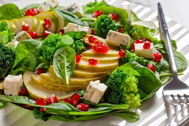 Birnensalat mit blauschimmelkäsewürfeln, brokkoli, spinat, getrockneten cranberry- und granatapfelkernen auf einem teller auf einem marmortisch, thanksgiving-beilage, horizontale ansicht von oben, nahaufnahme, makro