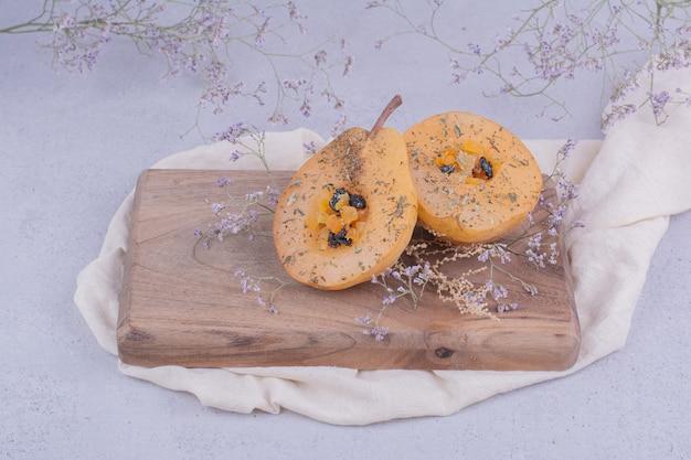 Birnenscheiben mit kräutern und gewürzen auf einem holzbrett