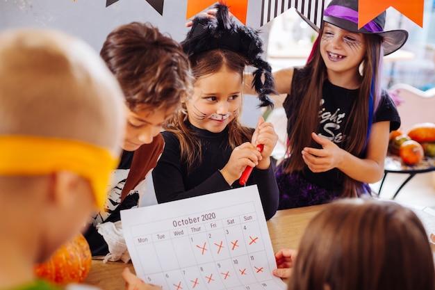 Bis zum anfang. gesellschaft von kindern mit bemalten gesichtern kann nicht bis zum beginn der halloween-party warten