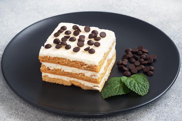 Biskuitkuchen mit buttercreme und minzschokoladenstücken auf einem schwarzen teller. dessert zum feiern oder geburtstagsfeier.