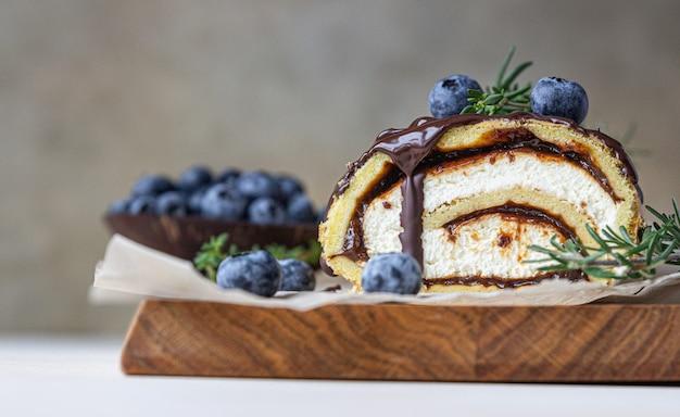 Biskuitrolle mit schokolade und frischkäse mit schokoladenglasur, heidelbeere und rosmarin.
