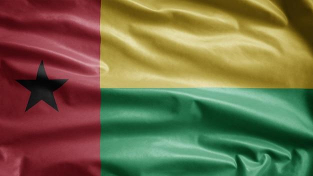 Bissau guineische flagge weht im wind. nahaufnahme von guinea bisau banner weht, weiche und glatte seide. stoff textur fähnrich hintergrund. verwenden sie es für das konzept für nationalfeiertage und länderanlässe.