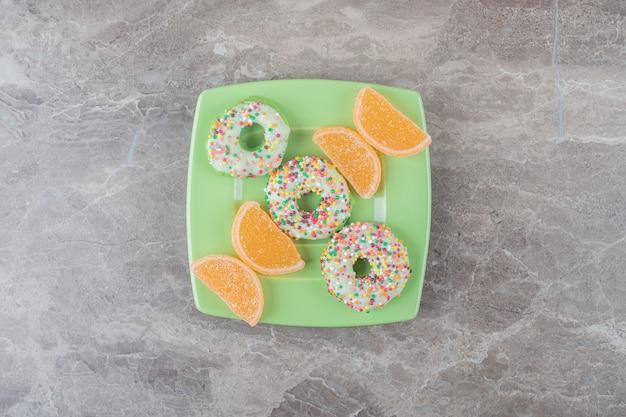 Bissengroße donuts und marmeladen auf einer grünen platte auf marmoroberfläche