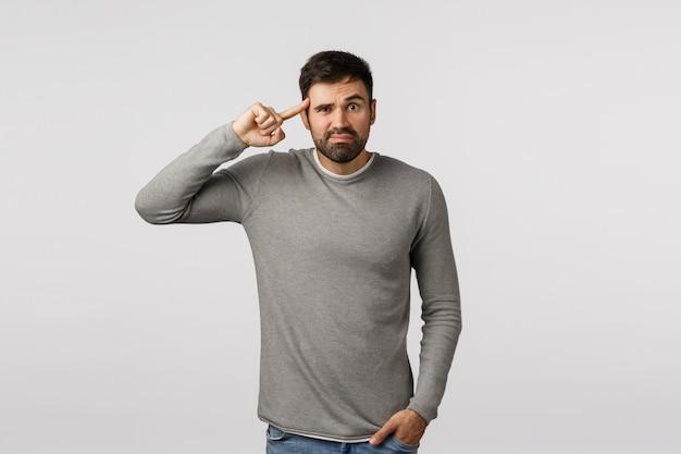 Bist du verrückt, hast den verstand verloren? verärgerter und genervter beunruhigter bärtiger männlicher mitarbeiter, rollender zeigefinger auf der schläfe und irritierter blick, höre dumme frage, reagiere auf dumme idee