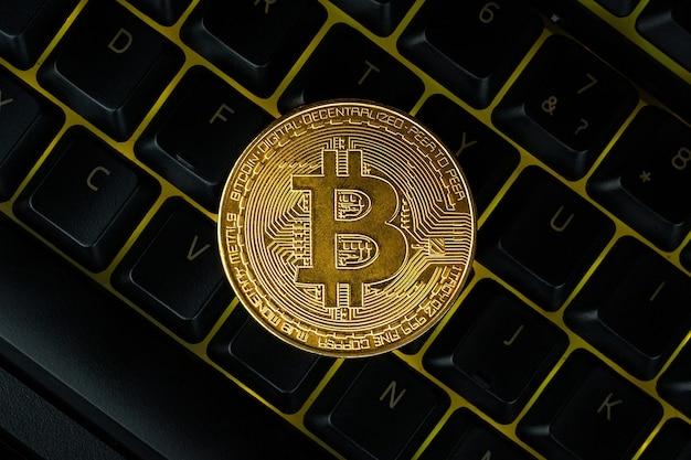 Bitcoin auf compuer-tastatur im hintergrund, symbol für elektronisches virtuelles geld und mining-kryptowährungskonzept.