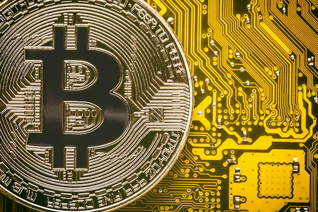 Bitcoin auf dem gelben computerkreislauf-motherboardabschluß oben.