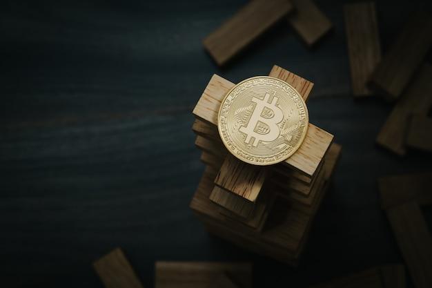 Bitcoin auf dem hölzernen bausteinturm. konzept für bitcoin-risiko oder bitcoin-strategie