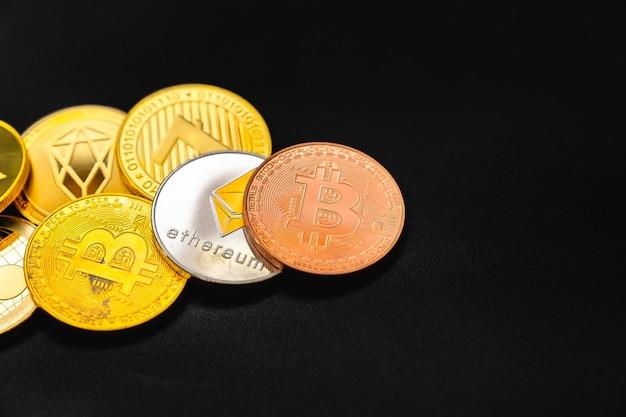 Bitcoin auf einem dunklen tisch. viele kryptowährungsmünzen