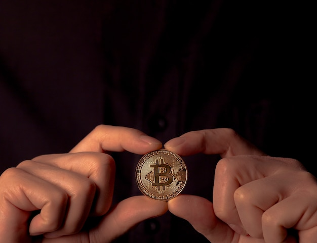 Bitcoin btc goldmünze in männlichen händen über schwarzem hintergrund. bit-kryptowährung mit kopienraum für text oben