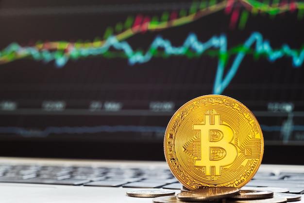 Bitcoin btc-kryptowährungen mit der anzeige von tradining-graph-laptops im hintergrund.