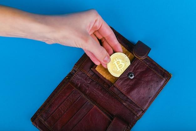 Bitcoin-diebstahl-konzept. eine hand stiehlt bitcoin aus einer brieftasche. platz zum schreiben.