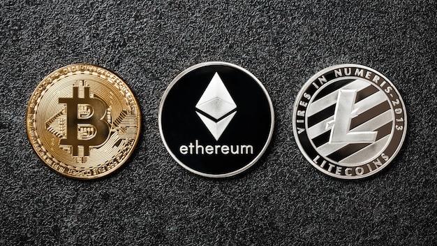 Bitcoin, ethereum, litecoin-münzen auf schwarzem hintergrund