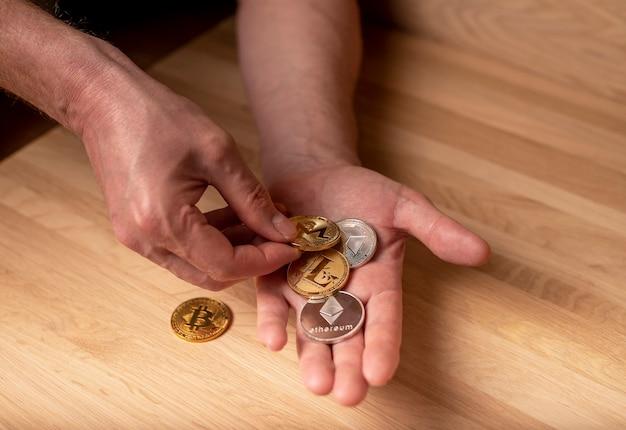 Bitcoin, etherium, eth, litecoin gold- und silbermünze in männlicher hand. kryptowährung und kryptoinvestition.