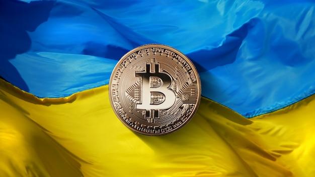 Bitcoin gold auf einem ukrainischen flaggenhintergrund. staatliche regulierung des kryptowährungsmarktes. die ukraine ist eines der fünf am schnellsten wachsenden länder der welt auf dem markt für kryptowährungen. kryptowährung