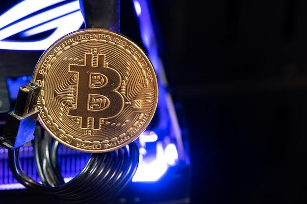 Bitcoin goldene münzen auf einer gpu mit neonlicht. die zukunft des geldes.