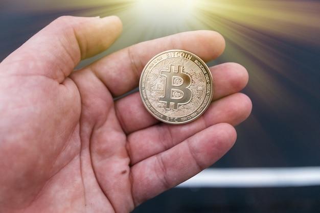Bitcoin goldene token-münze in einer kaukasischen männlichen hand