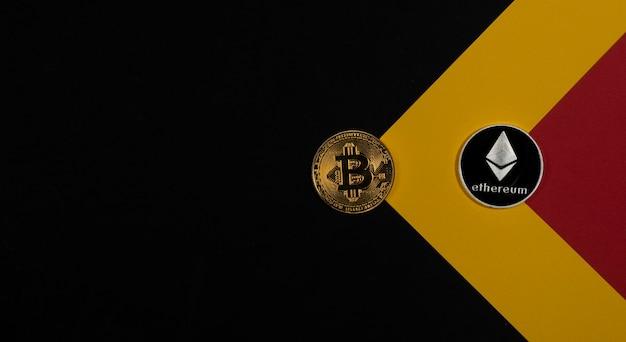 Bitcoin-goldmünze und ethereum-silber auf schwarzem hintergrund mit kopienraum für text.
