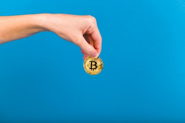 Bitcoin in der hand. bitcoin-aufbewahrungskonzept. platz für eine inschrift. bitcoin und hand. beitrag zur zukunft