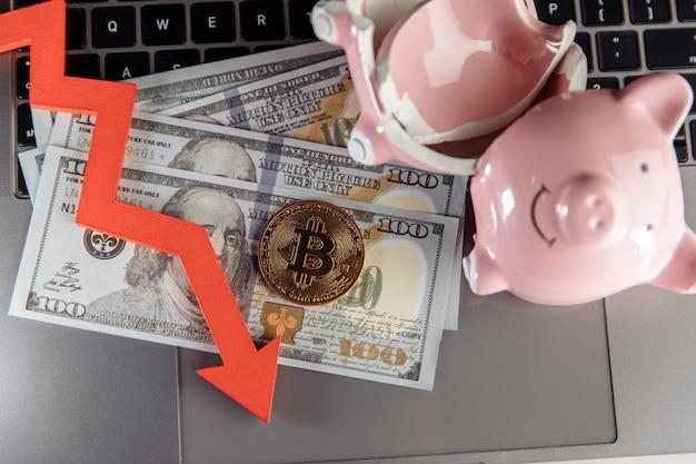 Bitcoin, kaputtes sparschwein und pfeil nach unten auf dollar-bargeld