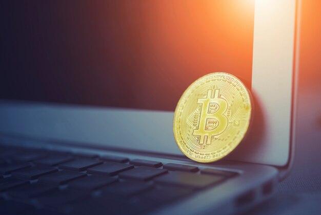 Bitcoin-konzept. goldener bitcoin setzte laptoptastatur mit leerem bildschirm mit licht an