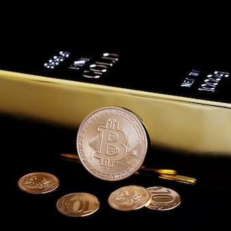 Bitcoin-kryptowährung und goldbarren auf einem schwarzen feld.
