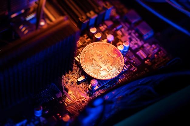 Bitcoin-kryptowährungsmünze auf einem pc-computer-motherboard, kryptowährungs-mining-konzept.