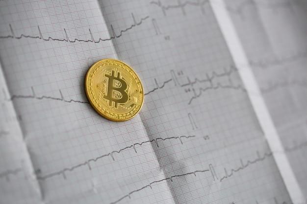 Bitcoin lebt. die goldmünze liegt auf einem papier