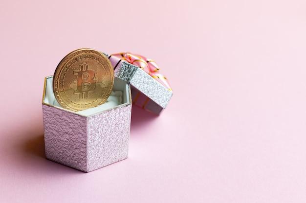 Bitcoin liegt an der kleinen geschenkbox auf rosa hintergrund.