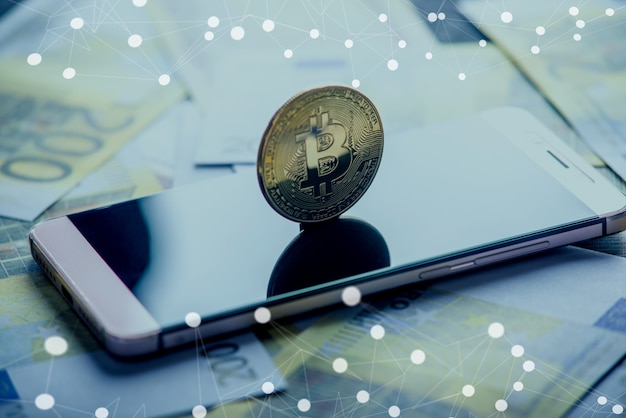 Bitcoin-münze auf dem telefonbildschirm auf dem hintergrund der eurobanknoten. blockchain und die zukunft der kryptowährung