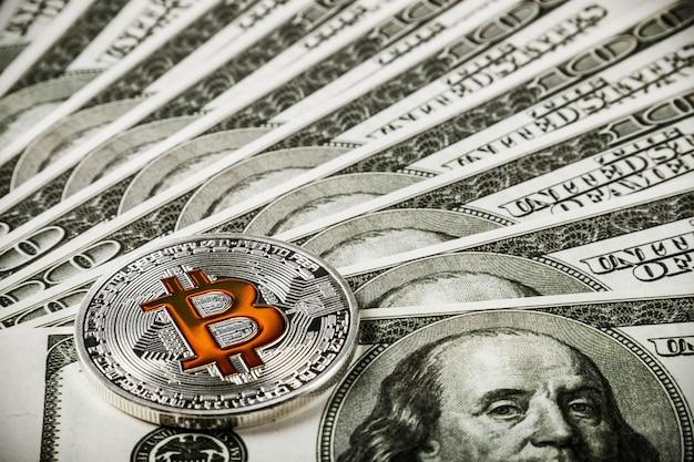 Bitcoin-münze auf hintergrund von banknoten von dollar