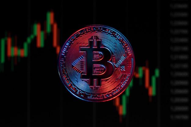 Bitcoin-münze auf schwarzem hintergrund mit grafik