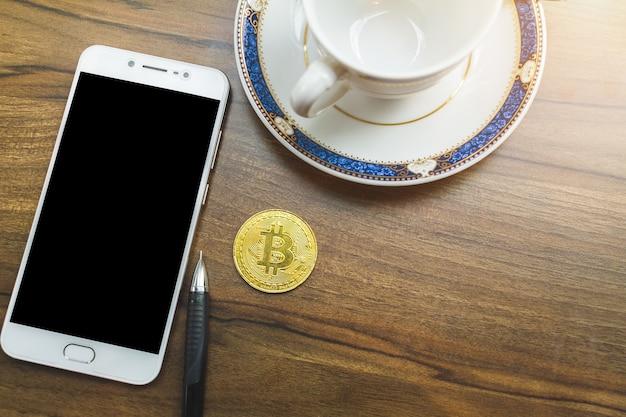 Bitcoin-münze auf smartphone, stift und kaffeetasse auf altem hölzernem schreibtisch auf die oberseite.