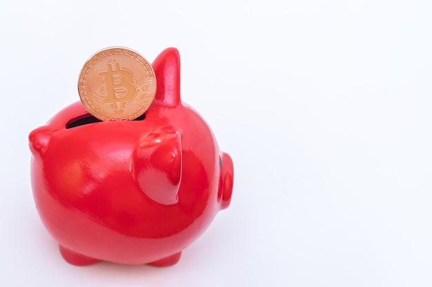 Bitcoin-münze in einem roten sparschwein auf einem weißen hintergrund. bitcoin-kryptowährungskonzept. virtuelles währungskonzept.