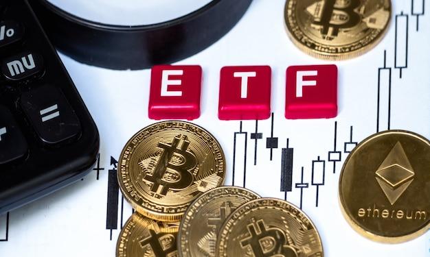 Bitcoin-münze in krypto-währung. mit etf-text und lupe auf papier mit kerzenständer