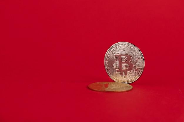 Bitcoin-münze, kryptogeld auf rotem grund. platz kopieren.
