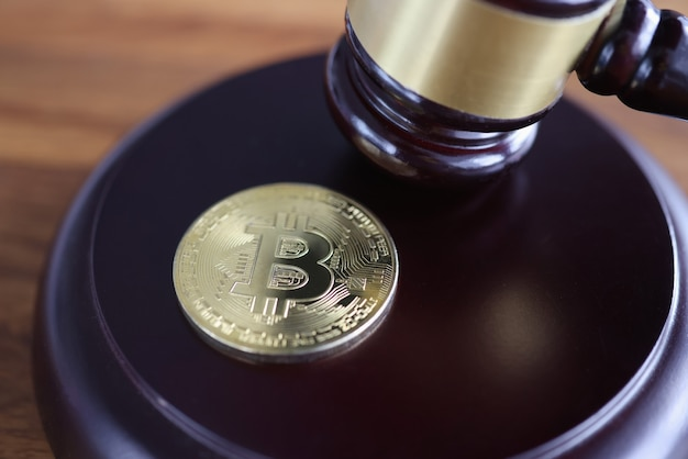 Bitcoin-münze liegt neben hölzernem richterhammer