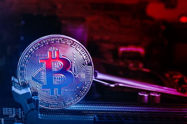 Bitcoin-münze mit abstraktem rotglühen-motherboard und roten blaulichtern.