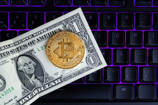 Bitcoin-münze mit laptop und us-dollar. bitcoin goldene münzen auf einem dollar laptop banknoten büro hintergrund schwarz laptop handy.