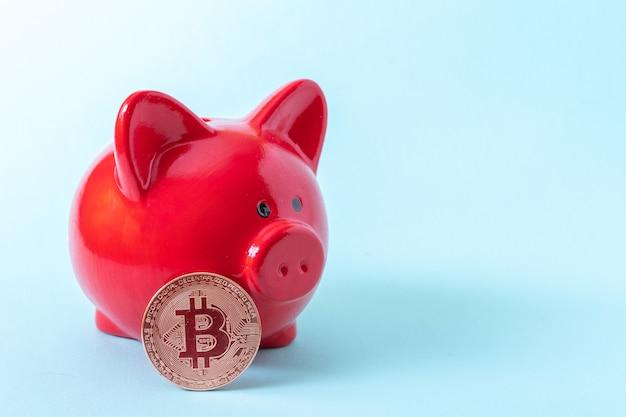 Bitcoin-münze und rotes sparschwein auf blauem hintergrund, nahaufnahme, kopienraum. kryptowährungs-speicherkonzept. neues virtuelles elektronisches und digitales geld