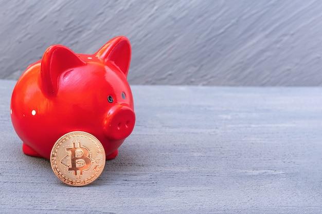 Bitcoin-münze und rotes sparschwein auf grauem hintergrund, nahaufnahme, kopienraum. kryptowährungs-speicherkonzept. neues virtuelles elektronisches und digitales geld