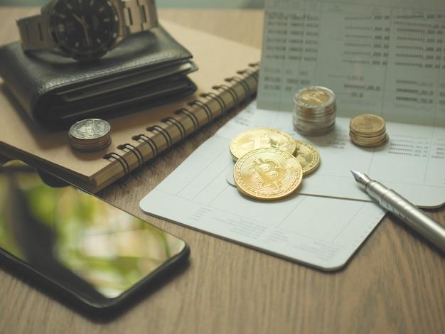 Bitcoin-münze und sparbuch und stift und smartphone auf tischgebrauch für geschäftskonzept