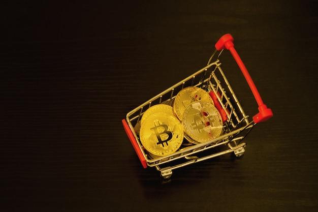 Bitcoin-münzen im warenkorb, schwarze oberfläche